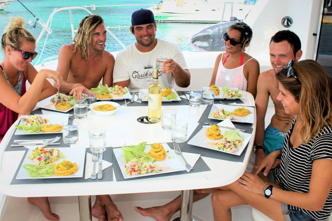 Friends eating food onboard kite cruise catamaran